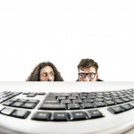 Two nerds staring at a keyboard